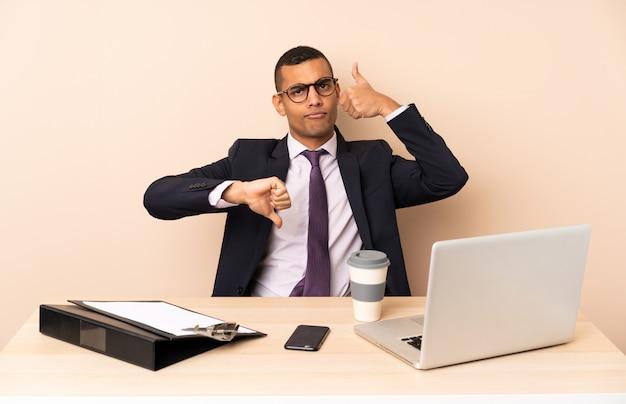 Uomo d'affari giovane nel suo ufficio con un computer portatile e altri documenti facendo segno buono-cattivo. indeciso tra sì o no