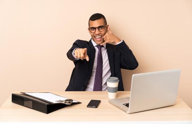 Giovane uomo d'affari nel suo ufficio con un computer portatile e altri documenti che fanno il gesto del telefono e che punta davanti