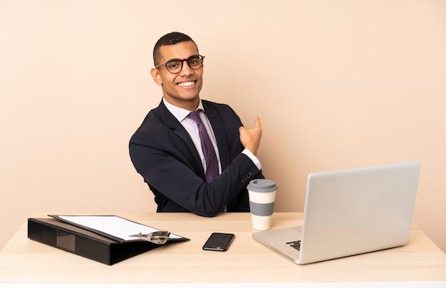 Uomo d'affari giovane nel suo ufficio con un computer portatile e altri documenti che punta indietro