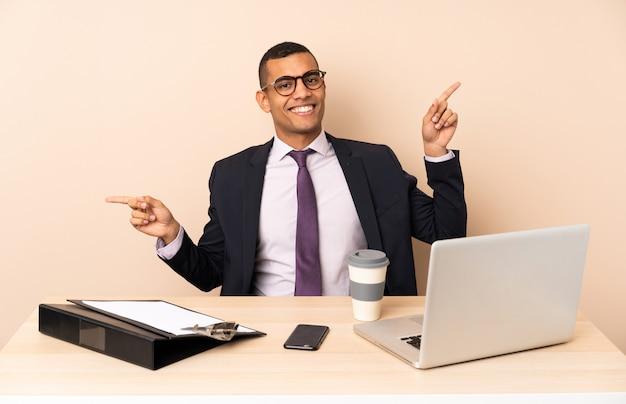 Uomo d'affari giovane nel suo ufficio con un computer portatile e altri documenti che punta il dito verso i laterali e felice