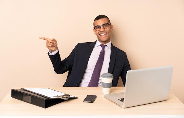 Uomo d'affari giovane nel suo ufficio con un computer portatile e altri documenti che punta il dito verso il lato e presentare un prodotto