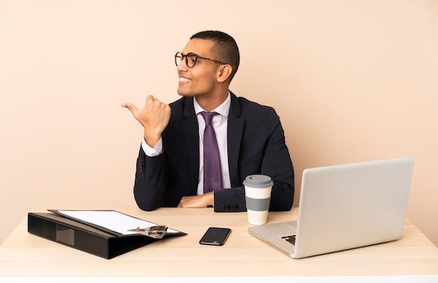 Uomo d'affari giovane nel suo ufficio con un computer portatile e altri documenti che punta verso il lato per presentare un prodotto
