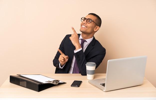 Uomo d'affari giovane nel suo ufficio con un computer portatile e altri documenti che indicano con il dito indice una grande idea