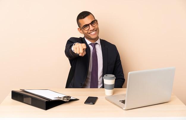 Il giovane uomo di affari nel suo ufficio con un computer portatile e altri documenti indica il dito con un'espressione sicura