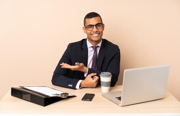 Uomo d'affari giovane nel suo ufficio con un computer portatile e altri documenti che presentano un'idea mentre guardando sorridente verso