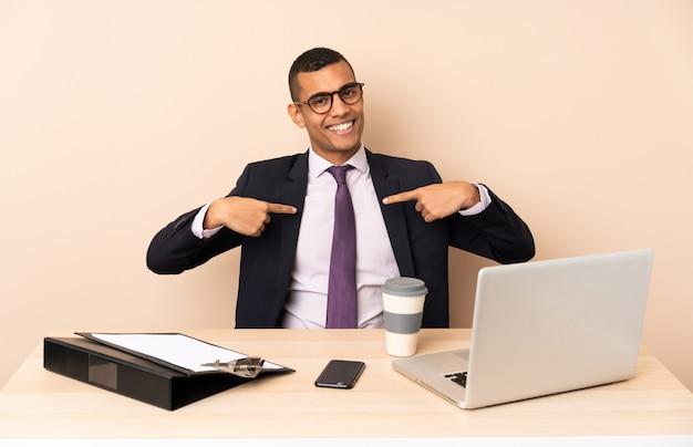 Uomo d'affari giovane nel suo ufficio con un computer portatile e altri documenti orgoglioso e soddisfatto di sé