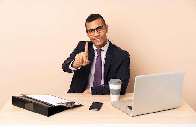 Uomo d'affari giovane nel suo ufficio con un computer portatile e altri documenti che mostrano e sollevando un dito