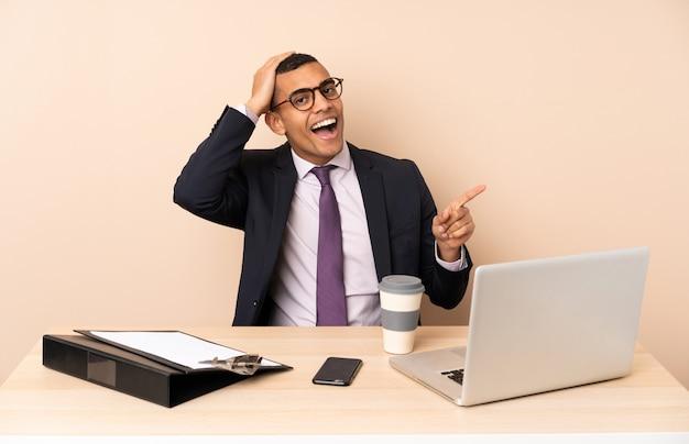 Uomo d'affari giovane nel suo ufficio con un computer portatile e altri documenti sorpreso e puntando il dito verso il lato