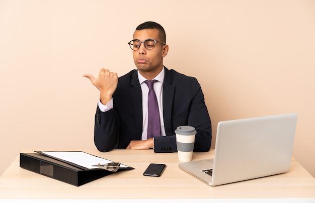 Uomo d'affari giovane nel suo ufficio con un computer portatile e altri documenti infelici e che punta verso il lato