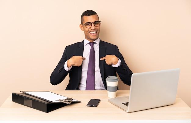 Uomo d'affari giovane nel suo ufficio con un computer portatile e altri documenti con sorpresa espressione facciale