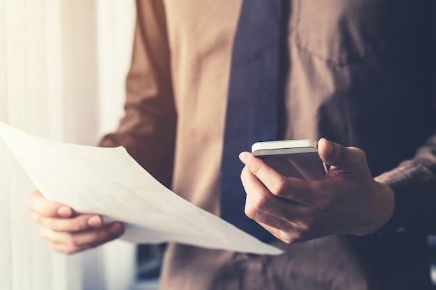 Giovane uomo d'affari azienda carta e l'utilizzo di smartphone in ufficio con la luce del sole. filtro tonico vintage.