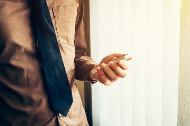 Giovane uomo d'affari che tiene smartphone in ufficio con la luce del sole. filtro tonico vintage.