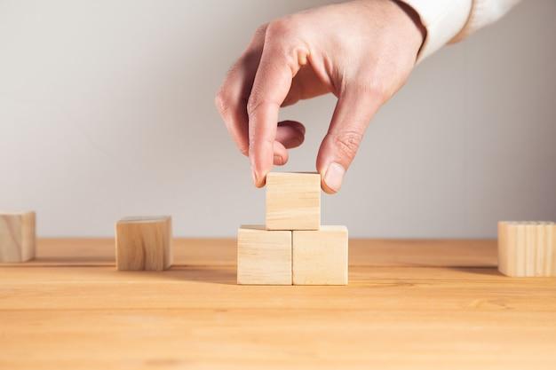 Giovane uomo di affari che tiene i cubi di legno.