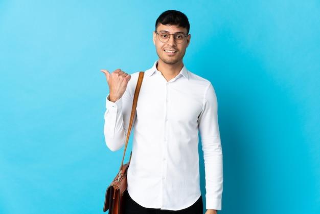 Giovane uomo d'affari isolato su blu che punta al lato per presentare un prodotto