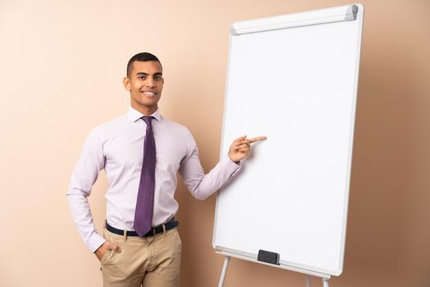 Uomo d'affari giovane sul muro isolato dando una presentazione sul bordo bianco e puntandolo
