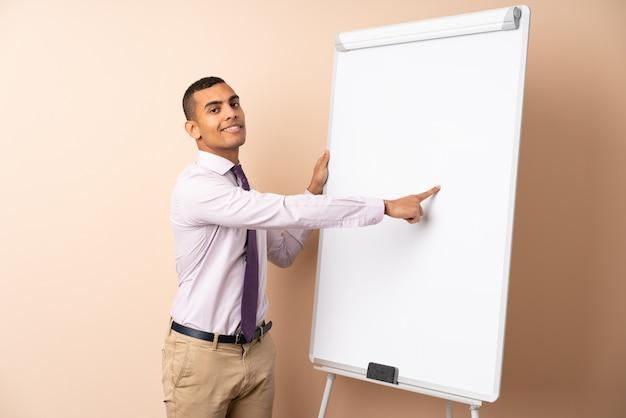 Uomo d'affari giovane sul muro isolato dando una presentazione sul bordo bianco e scrivere in esso