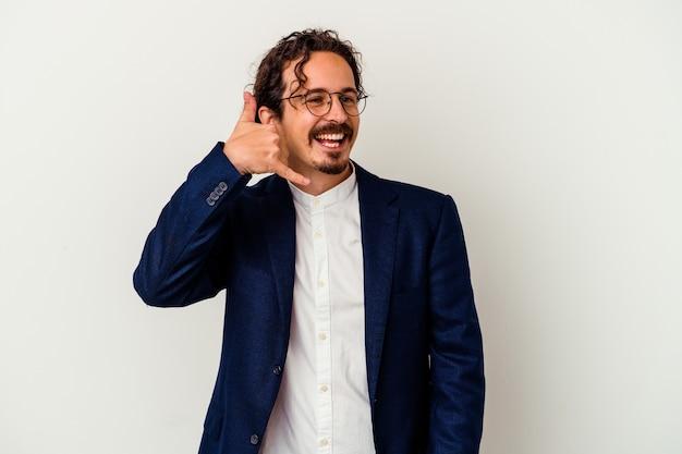 Giovane uomo d'affari isolato su sfondo bianco che mostra un gesto di chiamata di cellulare con le dita.