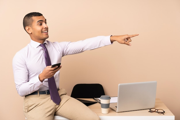 Uomo d'affari giovane in un ufficio che punta il dito verso il lato