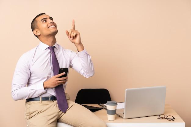 Uomo d'affari giovane in un ufficio che puntava il dito indice una grande idea