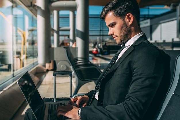 Uomo d'affari giovane seduto sul computer con la valigia in aeroporto in attesa del volo