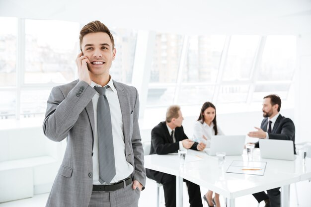 Giovane uomo d'affari che parla al telefono in ufficio con i colleghi al tavolo