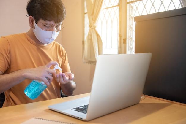 Giovane uomo d'affari con gli occhiali sta premendo alcol per pulire la mano, lavorando sul computer portatile a casa, l'evento di crisi del virus corona, covid19