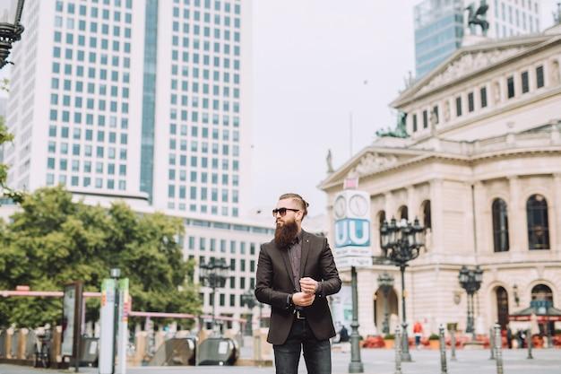 Il giovane uomo d'affari con la barba è in città