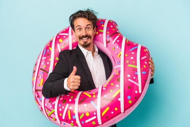 Giovane uomo di affari con la ciambella gonfiabile isolata su fondo blu che sorride e che alza pollice su
