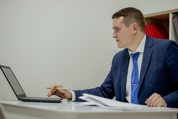 Uomo d'affari giovane che lavora a casa con laptop e documenti sulla scrivania.