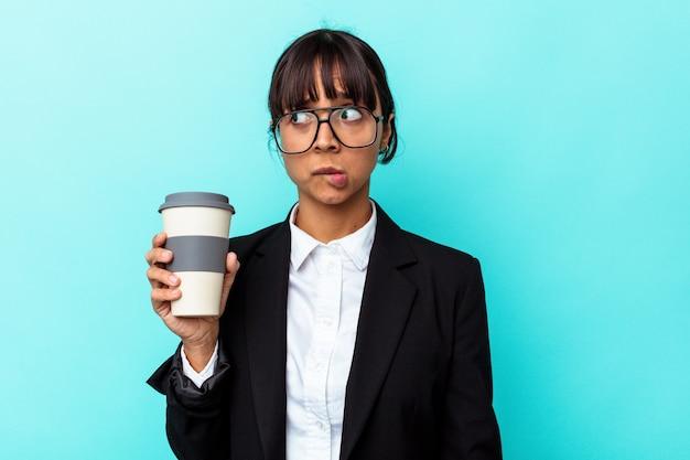 Giovane donna d'affari di razza mista che tiene un caffè isolato su sfondo blu confuso, si sente dubbioso e incerto.