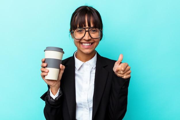 Giovane donna d'affari di razza mista che tiene un caffè isolato su sfondo blu sorridente e alzando il pollice