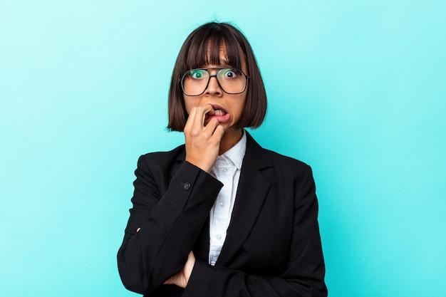 Giovane donna di razza mista d'affari isolata su sfondo blu che si morde le unghie, nervosa e molto ansiosa.