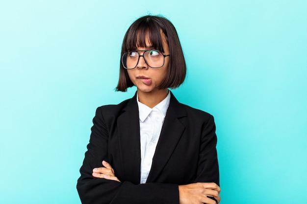 Giovane donna di razza mista d'affari isolata su sfondo blu confusa, si sente dubbiosa e insicura.
