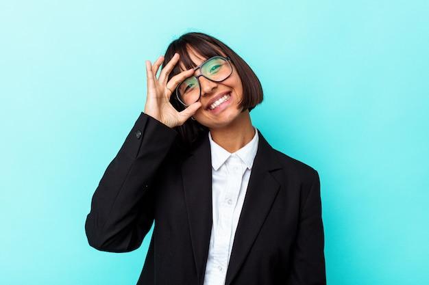 Giovane donna di razza mista d'affari isolata su sfondo blu eccitata mantenendo il gesto ok sull'occhio.