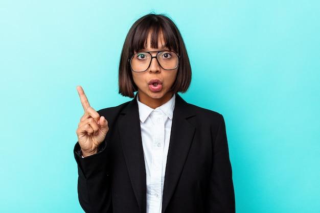 Giovane donna di razza mista d'affari isolata su sfondo blu con qualche grande idea, concetto di creatività.