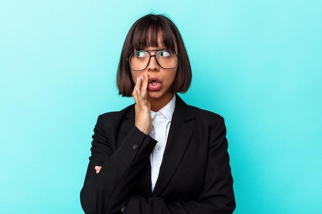 La giovane donna di razza mista d'affari isolata su sfondo blu sta dicendo una notizia segreta di frenata calda e guardando da parte