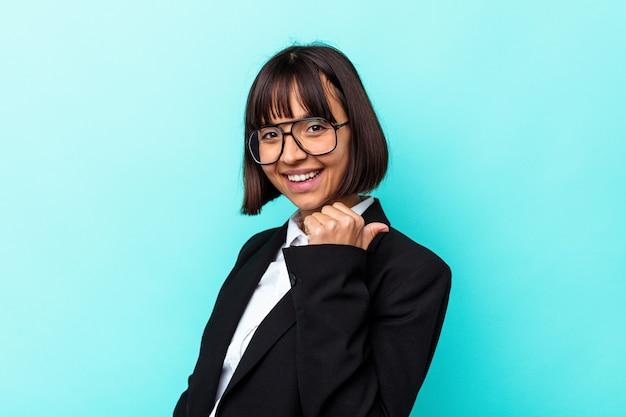 La giovane donna di razza mista d'affari isolata su sfondo blu punta con il pollice lontano, ridendo e spensierato.