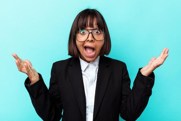 Giovane donna di razza mista d'affari isolata su sfondo blu che riceve una piacevole sorpresa, eccitata e alzando le mani.