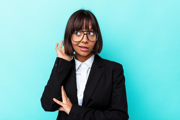 Giovane donna di razza mista d'affari isolata su sfondo blu cercando di ascoltare un pettegolezzo.