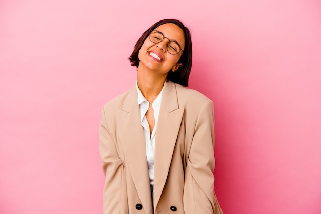 La giovane donna di razza mista d'affari isolata su sfondo rosa ride e chiude gli occhi, si sente rilassata e felice.