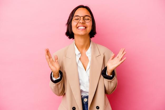 La giovane donna di razza mista d'affari isolata su sfondo rosa ride ad alta voce tenendo la mano sul petto.