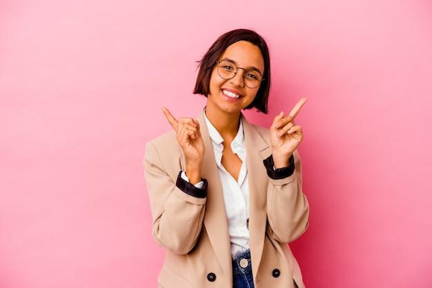 Young business donna di razza mista isolata su sfondo rosa che punta a diversi spazi di copia, scegliendo uno di loro, mostrando con il dito.