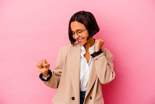 Donna di razza mista di giovani affari isolata sul muro rosa ballando e divertendosi.