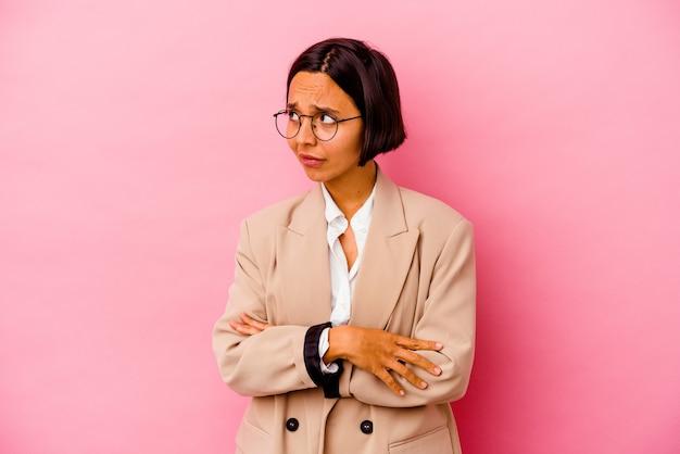 Donna di razza mista di giovani affari isolata sulla parete rosa che sogna di raggiungere obiettivi e scopi