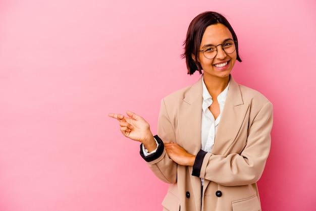 Young business donna di razza mista isolata sul muro rosa sorridendo allegramente indicando con l'indice di distanza