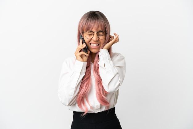 Giovane donna d'affari di razza mista con i capelli rosa che tiene in mano un cellulare isolato su sfondo rosa frustrato e che copre le orecchie