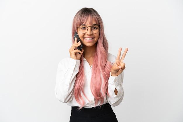 Giovane donna di razza mista d'affari con i capelli rosa che tiene in mano un cellulare isolato su sfondo rosa che sorride e mostra il segno della vittoria