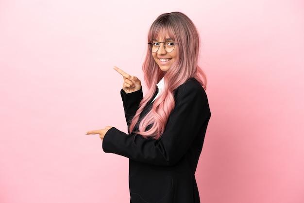 Giovane donna di razza mista d'affari con capelli rosa isolati su sfondo rosa che punta il dito di lato e presenta un prodotto