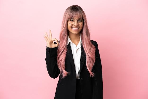 Giovane donna di razza mista d'affari con capelli rosa isolata su sfondo rosa che mostra segno ok con le dita