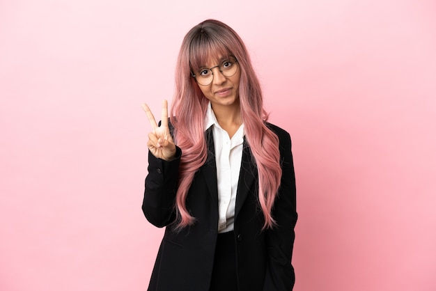 Giovane donna di razza mista d'affari con i capelli rosa isolata su sfondo rosa sorridente e che mostra il segno della vittoria